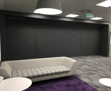 Smart lobby with stylish cream sofa on purple rug