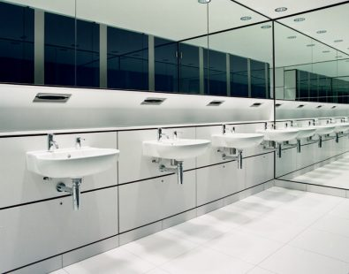 Row of bathroom sinks under mirror