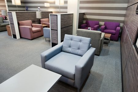 Stylish arm chairs in waiting area with laminate walls